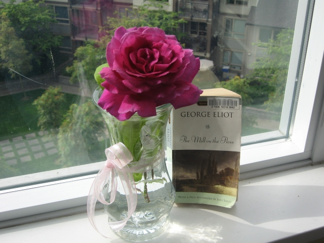 Rose in a vase beside a copy of The Mill on the Floss